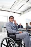 Homme d'affaires de sourire s'asseyant dans un fauteuil roulant images stock