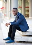Homme d'affaires de sourire s'asseyant dehors sur des étapes Images stock