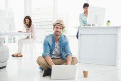 Homme d'affaires de sourire s'asseyant sur le plancher utilisant l'ordinateur portable Image stock
