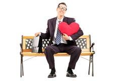 Homme d'affaires de sourire s'asseyant sur un banc en bois et tenant le rouge il photos libres de droits