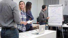 Homme d'affaires de sourire se dirigeant aux diagrammes sur le conseil de secousse tandis que ses collègues offrant des idées Images stock
