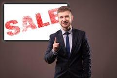 Homme d'affaires de sourire se tenant avec un sourire affecté et un aileron augmenté d'index Image libre de droits