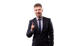 Homme d'affaires de sourire se tenant avec un sourire affecté et un aileron augmenté d'index Photos libres de droits
