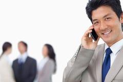 Homme d'affaires de sourire sur le téléphone portable et l'équipe Photographie stock
