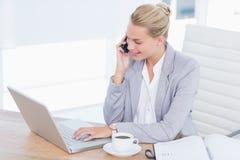Homme d'affaires de sourire téléphonant à son bureau tout en à l'aide de son ordinateur Images stock