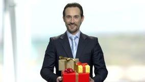 Homme d'affaires de sourire tenant des boîte-cadeau clips vidéos