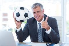 Homme d'affaires de sourire tenant le ballon de football avec des pouces  Images libres de droits