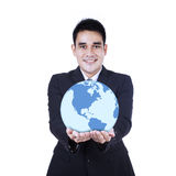 Homme d'affaires de sourire tenant un globe Photo stock