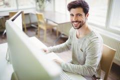 Homme d'affaires de sourire travaillant au bureau dans le bureau images stock