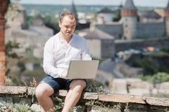 Homme d'affaires de sourire travaillant avec l'ordinateur portable au café de parc dehors Photos stock