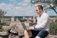 Homme d'affaires de sourire travaillant avec l'ordinateur portable au café de parc dehors Photo libre de droits