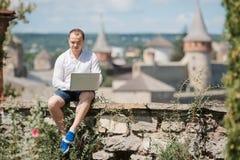 Homme d'affaires de sourire travaillant avec l'ordinateur portable au café de parc dehors Photographie stock