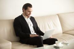 Homme d'affaires de sourire travaillant sur l'ordinateur portable éloigné de la maison Image stock