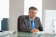 Homme d'affaires de sourire utilisant l'ordinateur au bureau Photo libre de droits