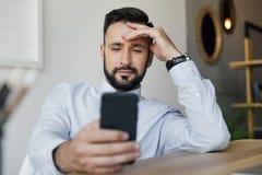 Homme d'affaires de sourire utilisant le smartphone tout en se reposant sur le lieu de travail Image libre de droits
