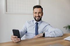 Homme d'affaires de sourire utilisant le smartphone tout en se reposant sur le lieu de travail Photos stock