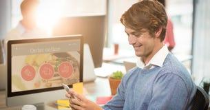 Homme d'affaires de sourire utilisant le téléphone portable au bureau d'ordinateur Images libres de droits