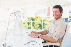 Homme d'affaires de sourire utilisant son ordinateur à son bureau Photos stock