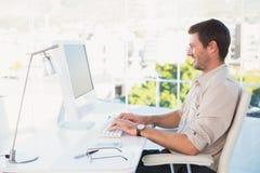 Homme d'affaires de sourire utilisant son ordinateur à son bureau Images libres de droits