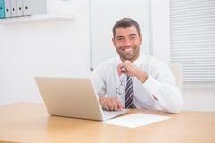 Homme d'affaires de sourire utilisant son ordinateur à son bureau Image libre de droits