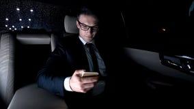 Homme d'affaires de sourire vérifiant l'email, utilisant le téléphone, se reposant sur le siège arrière de la voiture photographie stock libre de droits