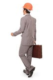 Homme d'affaires de vue arrière marchant avec le casque de constructeurs image stock