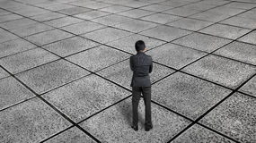 Homme d'affaires de vue arrière pensant et se tenant sur le flo carrelé sans fin Photos stock