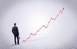 Homme d'affaires debout avec la flèche rouge de graphique Photographie stock libre de droits