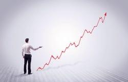 Homme d'affaires debout avec la flèche rouge de graphique Photos stock