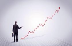 Homme d'affaires debout avec la flèche rouge de graphique Photo stock