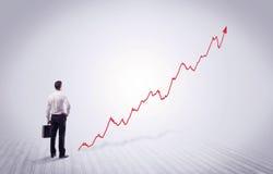 Homme d'affaires debout avec la flèche rouge de graphique Photographie stock