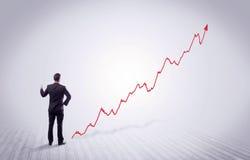 Homme d'affaires debout avec la flèche rouge de graphique Photo libre de droits