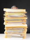 Homme d'affaires derrière la pile de fichiers Photographie stock