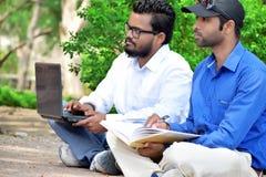 Homme d'affaires des jeunes deux utilisant l'ordinateur portable et le livre d'écriture dans extérieur images libres de droits