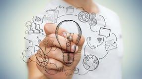Homme d'affaires dessinant une ampoule avec un stylo avec des icônes de multimédia Photographie stock libre de droits