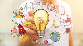 Homme d'affaires dessinant une ampoule avec un stylo avec des icônes de multimédia Photo libre de droits
