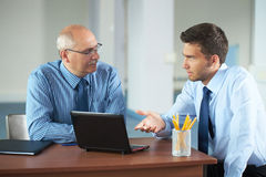 Homme d'affaires deux avec l'ordinateur portatif, pousse de bureau Photos stock