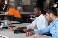 Homme d'affaires deux futé utilisant le workig de smartphone et d'ordinateur portable dans le bureau Image stock