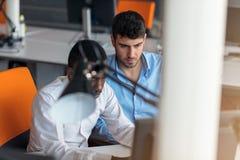 Homme d'affaires deux futé utilisant le workig de smartphone et d'ordinateur portable dans le bureau Photo libre de droits
