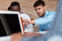 Homme d'affaires deux futé utilisant le workig de smartphone et d'ordinateur portable dans le bureau Images stock