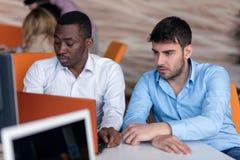 Homme d'affaires deux futé utilisant le workig de smartphone et d'ordinateur portable dans le bureau Image libre de droits