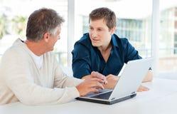Homme d'affaires deux travaillant sur leur ordinateur portatif Photographie stock