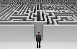 Homme d'affaires devant un labyrinthe énorme Photographie stock libre de droits