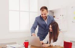 Homme d'affaires dirigeant le travail de son assistant féminin sur l'ordinateur portable photo libre de droits