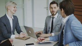 Homme d'affaires discutant le futur projet d'affaires avec les collègues masculins et féminins s'asseyant à la table dans le bure banque de vidéos