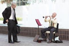 Homme d'affaires donnant l'argent au joueur d'instrument Images libres de droits