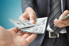 Homme d'affaires donnant l'argent - dollar d'Etats-Unis (U Image libre de droits
