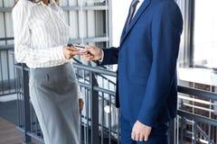 Homme d'affaires donnant la carte de crédit à la femme d'affaires photo stock
