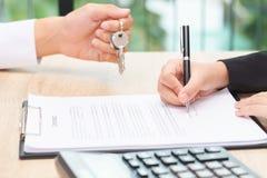 Homme d'affaires donnant la clé au-dessus du document de contrat avec le signe de client Image stock
