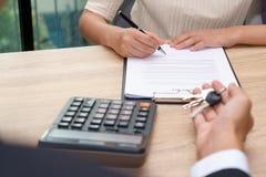 Homme d'affaires donnant la clé et le document de signature de convention de prêt de client Photographie stock